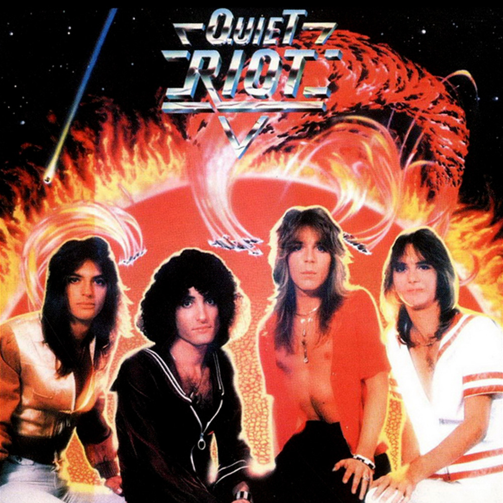 The self-titled debut from Quiet Riot was released in Japan in 1977. As to what is going on in the background on that album cover, your guess is as good as mine. From left to right: Drew Forsyth (drums), Kevin DuBrow (vocals, RIP), Randy Rhoads (guitar, RIP), and Kelly Garni (bass).