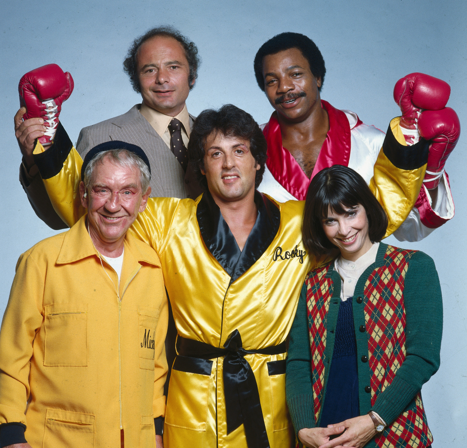 "Portrait of Sylvester Stallone, as Rocky Balboa, with the cast of the ""Rocky II"" movie. (From left) Burgess Meredith as Mickey Goldmill, Burt Young as Paulie, Carl Weathers as Apollo Creed, and Talia Shire as Adrian. Los Angeles, California 11/1978 (Image # 1147 )"