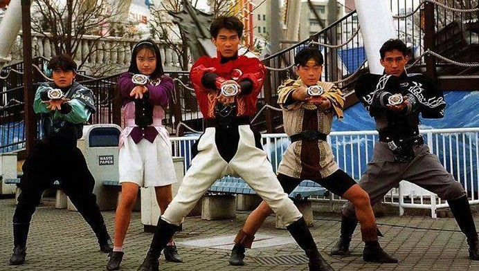 The Zyurangers preparing to transform using their Dino Bucklers. From left to right - Dan (blue), Mei (pink), Geki (red), Boi (yellow), and Goushi (black).